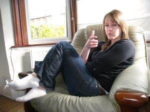 Een jonge vrouw die ontspannen op een stoel zit en met haar hand een pistool nadoet.